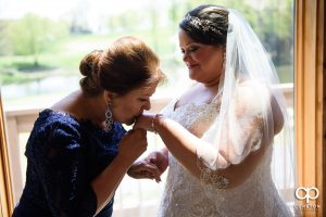 Bride's mom kissing her hand.