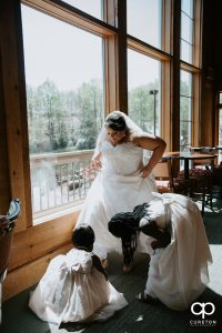 Bride being helped into her shoes.