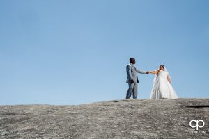 Bride and groom walking up a mountain side.