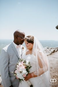 Groom touching foreheads with the bride near the cross at Glassy Chapel.