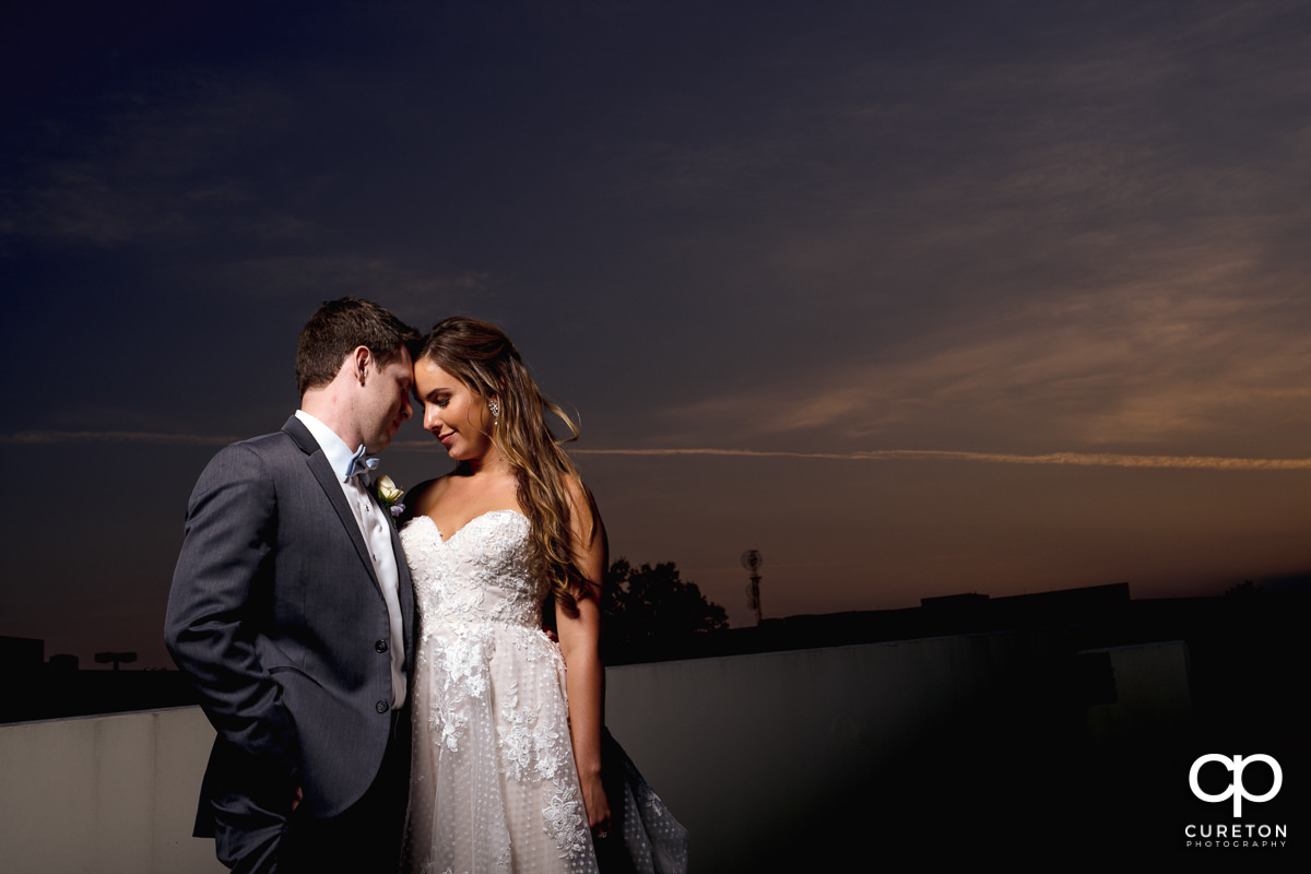 Bride and groom hugging on a rooftop at sunset in downtown Greenville at their Commerce Club wedding reception.