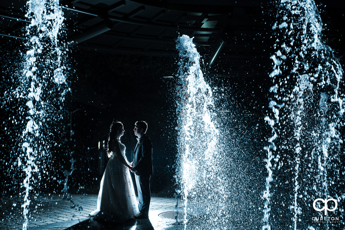 Bride and groom standing in the fountains at night after their wedding at the Commerce Club in Greenville,SC.