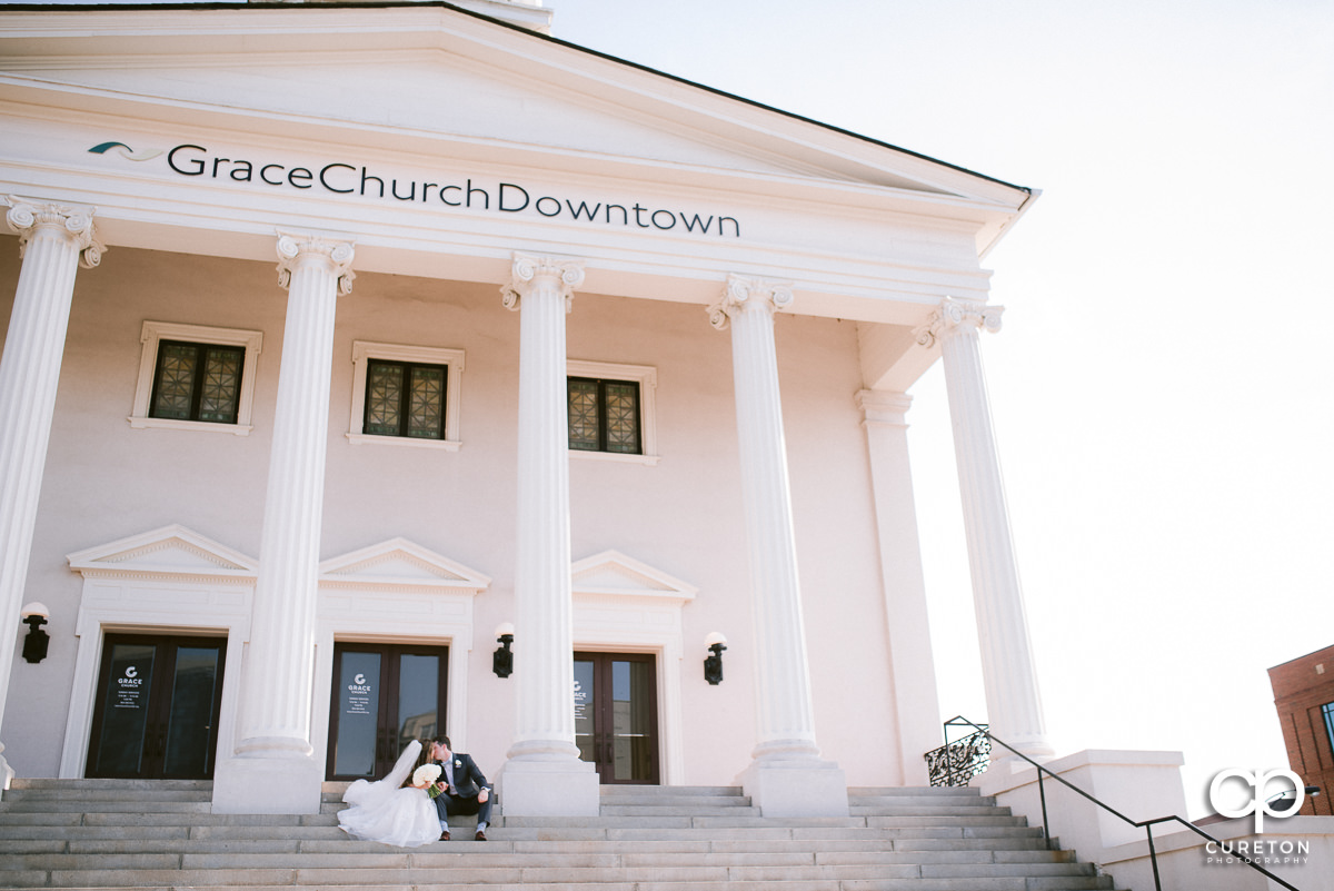 Bride and groom cuddling on the steps after their wedding at Grace Church in Greenville,SC.