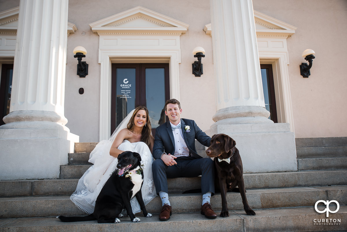 Bride and groom sitting with their dogs on the steps of Grace Church in downtown Greenville,SC.