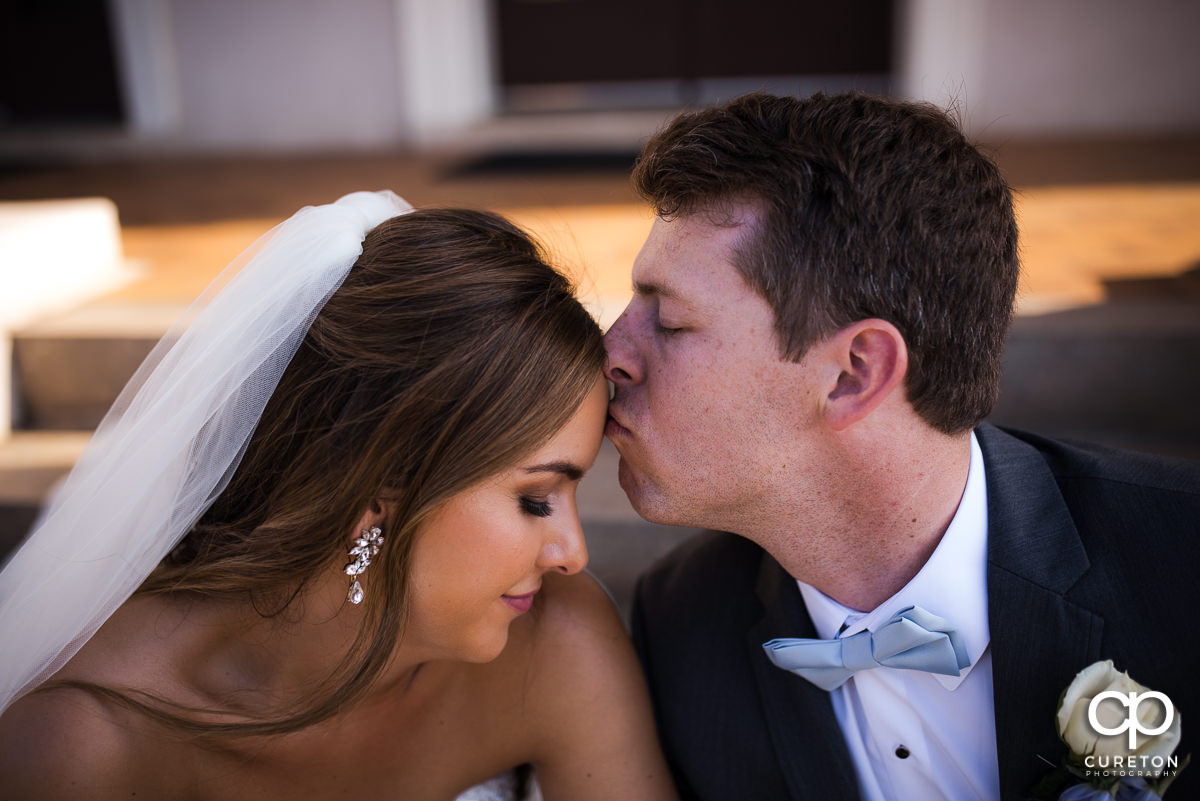 Groom kissing his bride on the forehead on the steps of Grace Church in Greenville,SC.