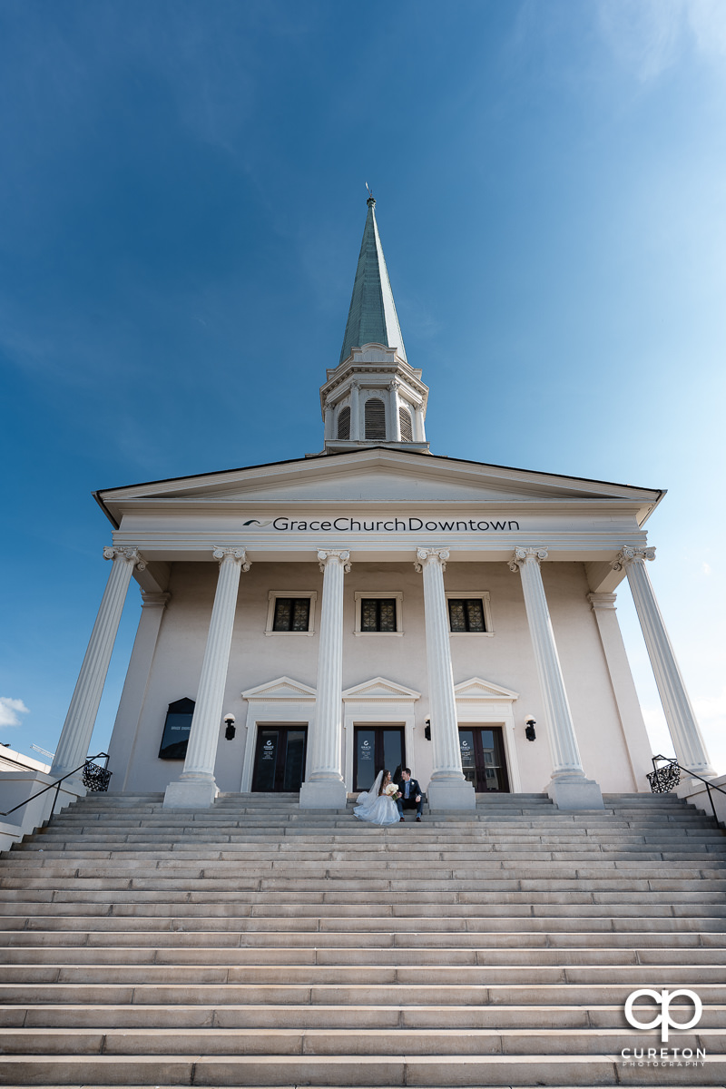 Bride and groom sitting on the steps outside of their Grace Church wedding in Greenville,SC.