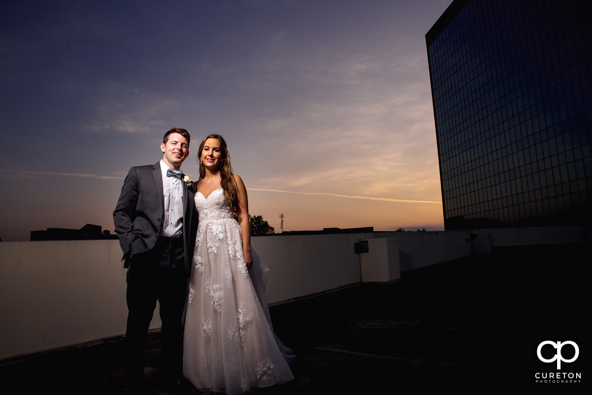 Bride and groom standing on a rooftop at sunset at their downtown Greenville,SC wedding.