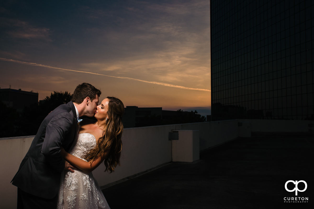 Groom dipping his bride on a rooftop at sunset at their Commerce Club wedding in Greenville,SC.