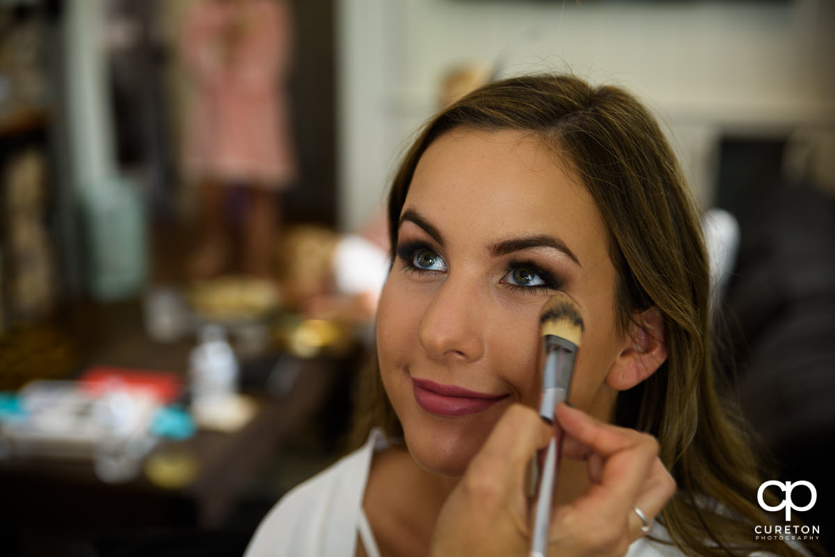 Bride having her makeup applied before the ceremony.