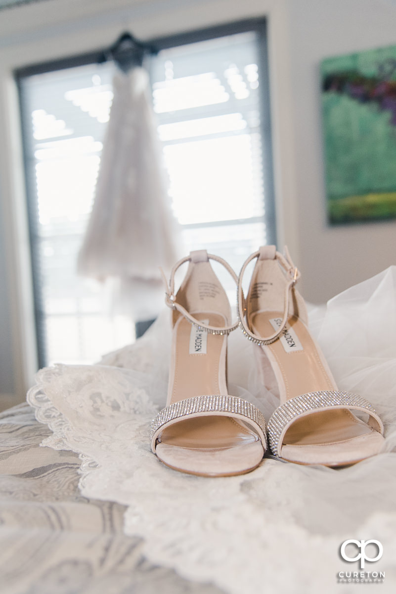 Bride's shoes with the dress hanging in the background.