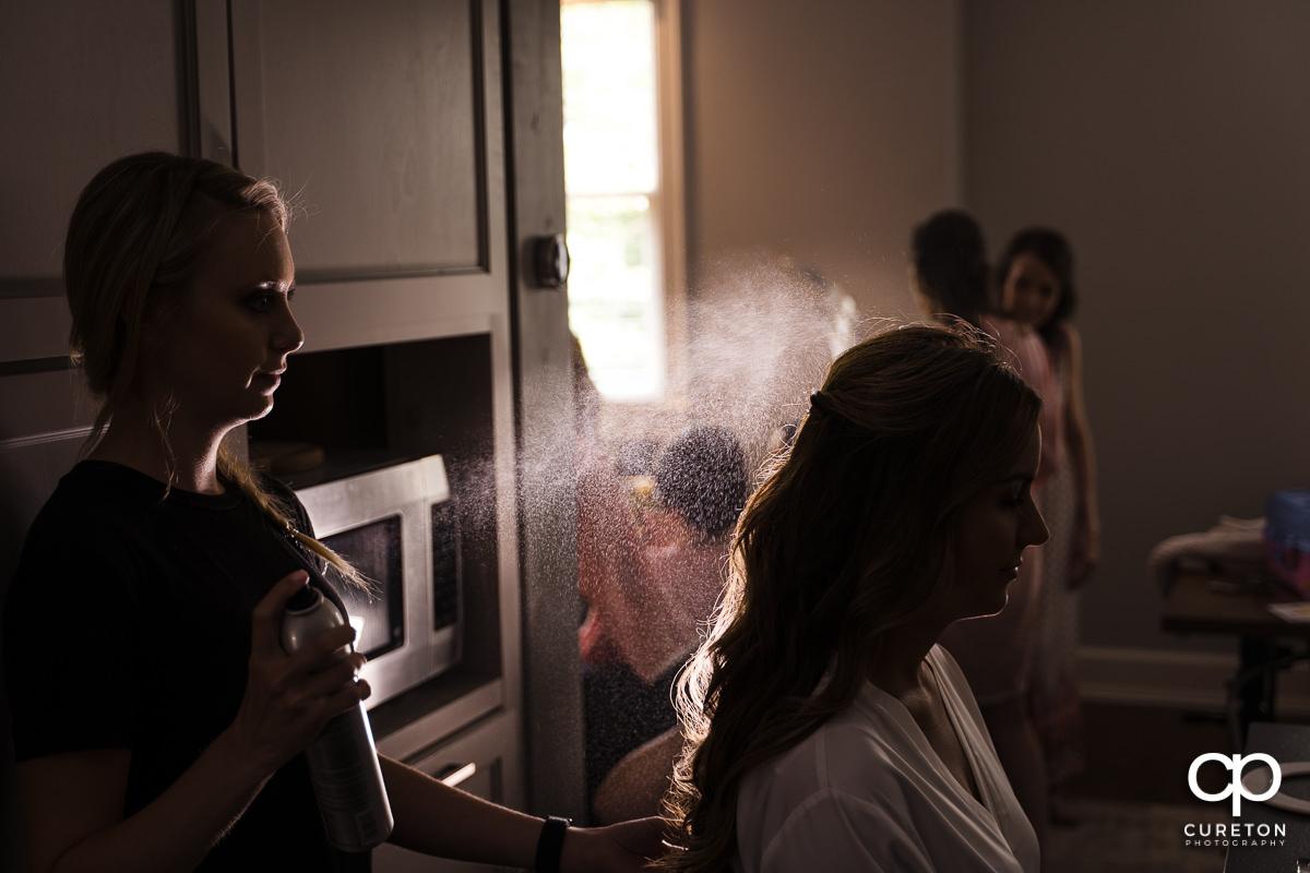 Bride's hair being sprayed before the wedding.