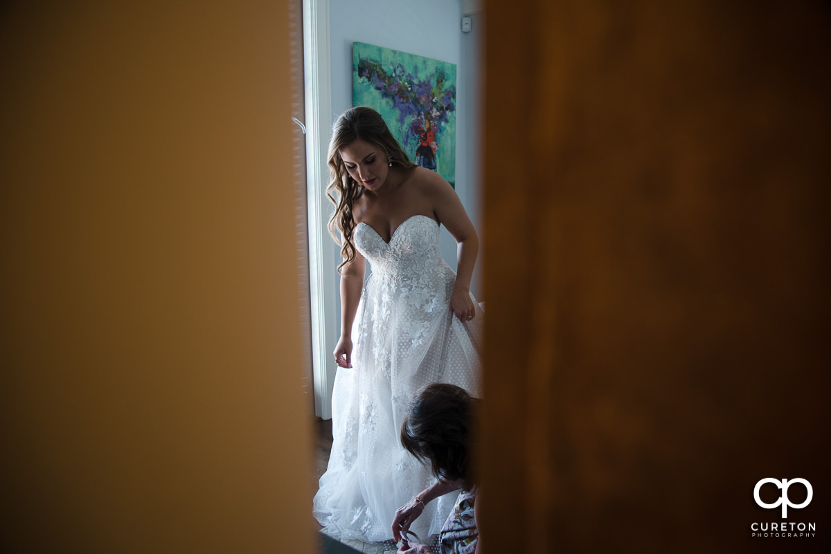 Bride getting help with her shoes.