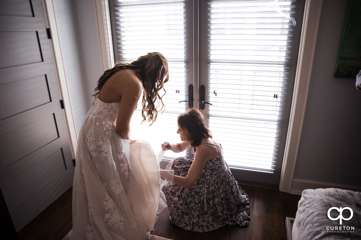 Bride's mother helping her put her shoes on.