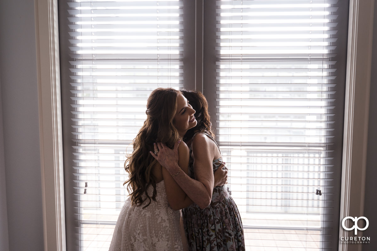 Bride and her mom hugging before the wedding at Grace Church in Greenville,SC.