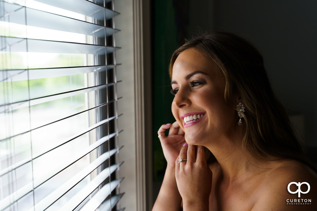 Bride smiling as she puts on her earrings.