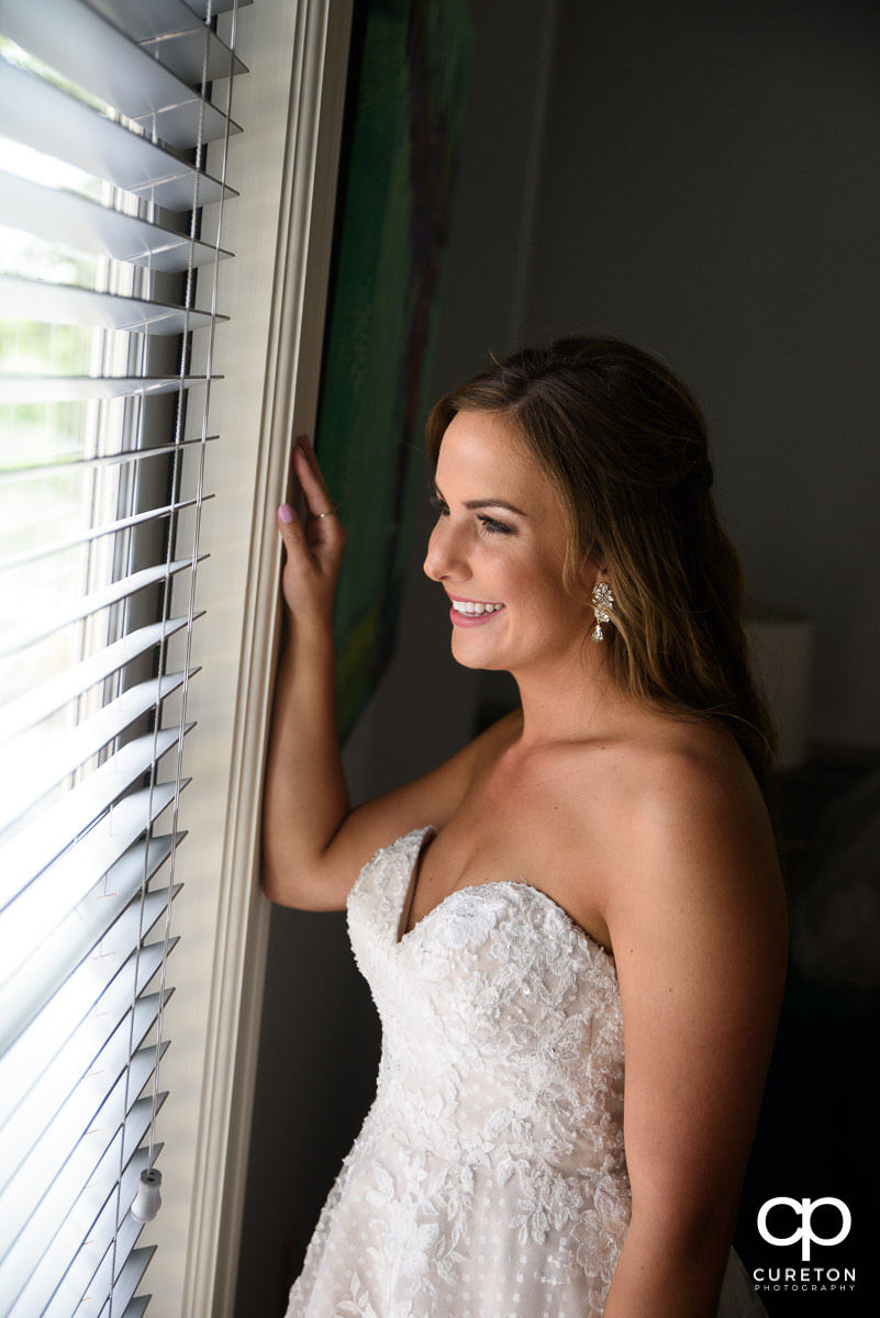 Bride looking out the window in her dress.