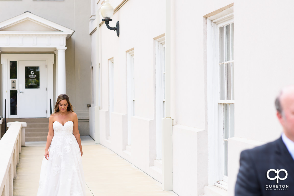 Bride walking up to a first look with her father.