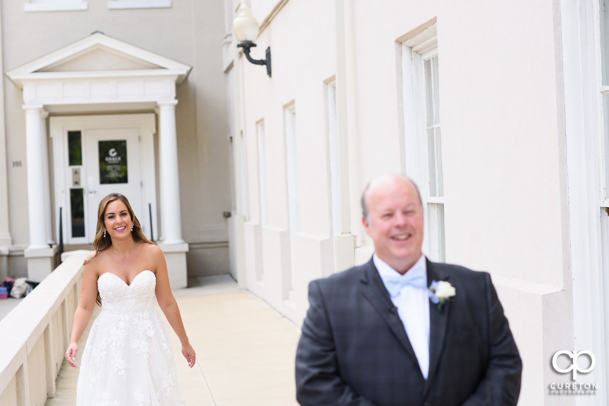 Bride smiling as she walks up behind her dad to show him her dress.