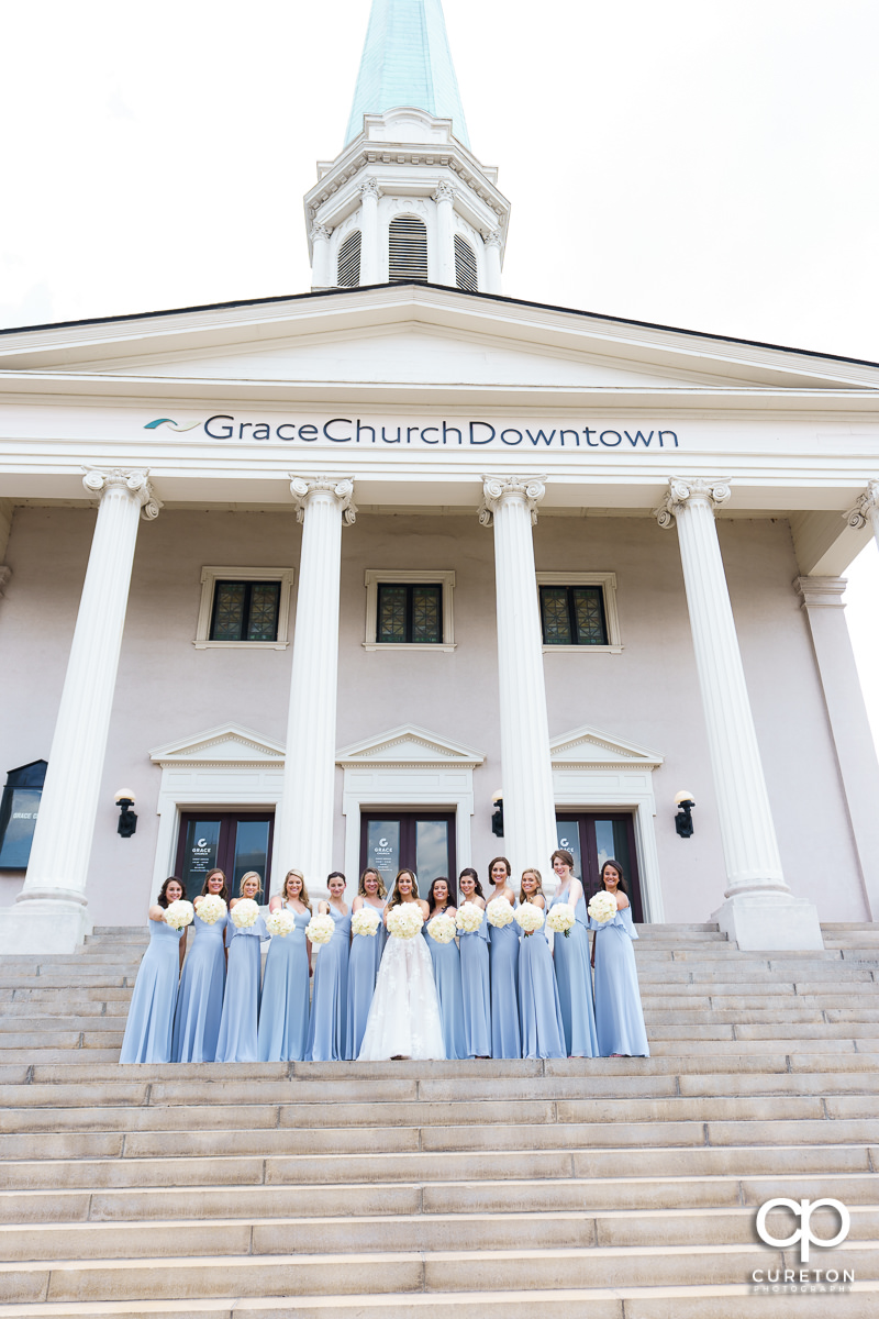 Bride and her bridesmaids holding out their flowers before the wedding at Grace Church in Greenville,SC.