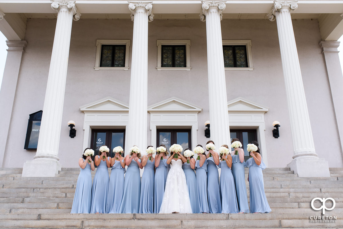 Bride and bridesmaids holding flowers over their faces on the steps before the wedding at Grace Church in Greenville,SC.