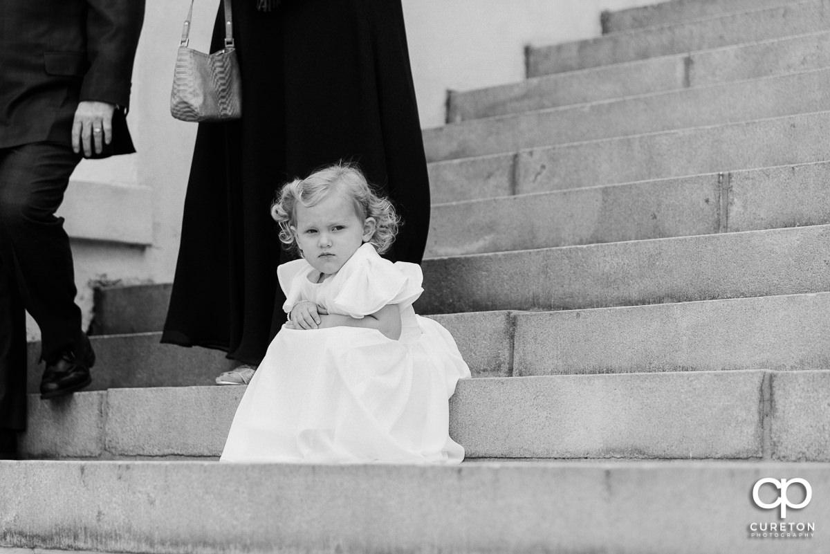 Flower girl sitting on some steps.
