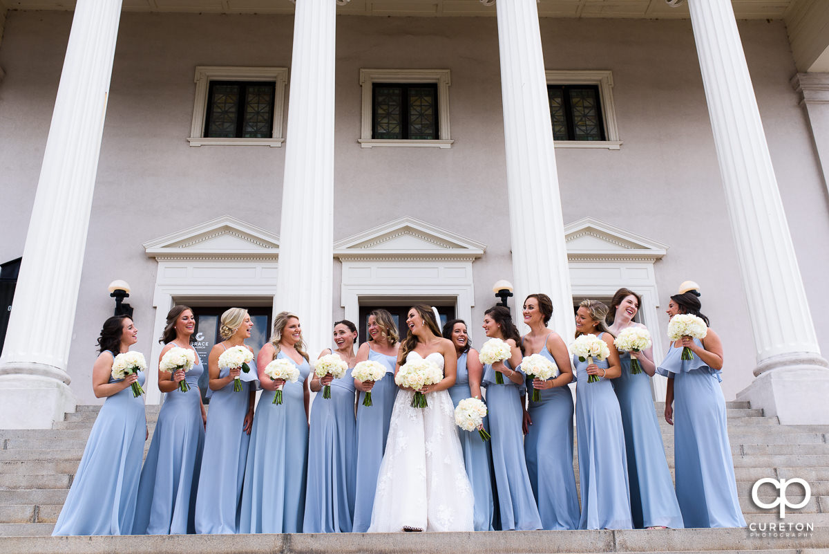 Bride laughing with her bridesmaids on the steps of Grace Church in Greenville.