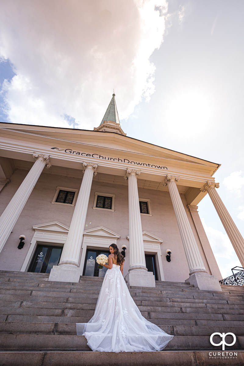 Bride walking up the steps holding her bouquet at the wedding at Grace Church in Greenville,SC.