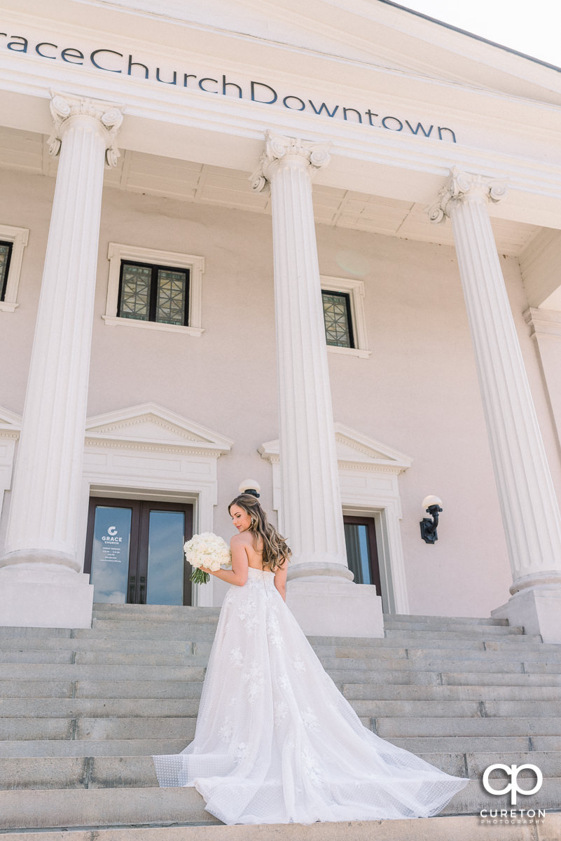 Bride looking at her bouquet on the steps at Grace Church.