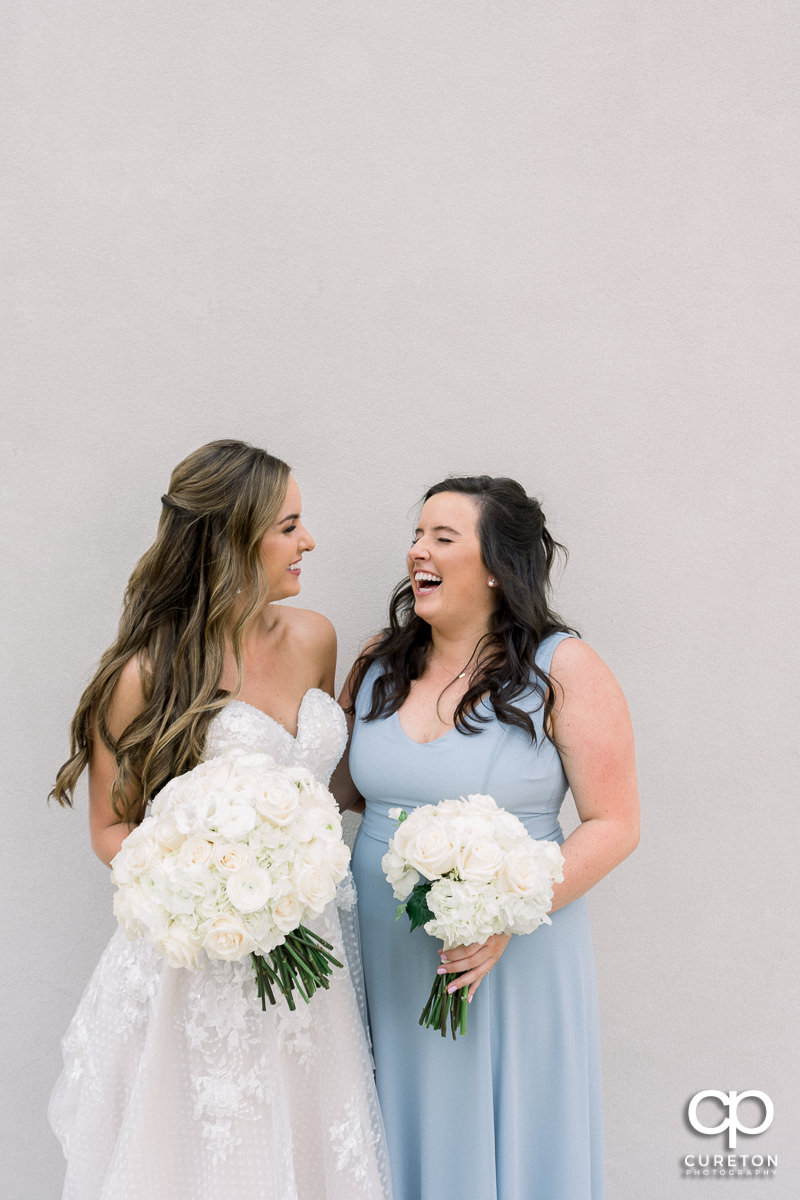 Bride laughing with her sister.
