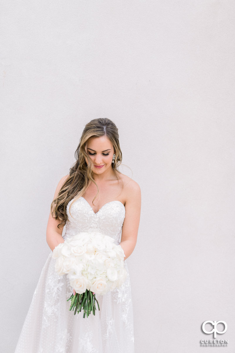 Bride against a white wall before her wedding at Grace Church in Greenville,SC.