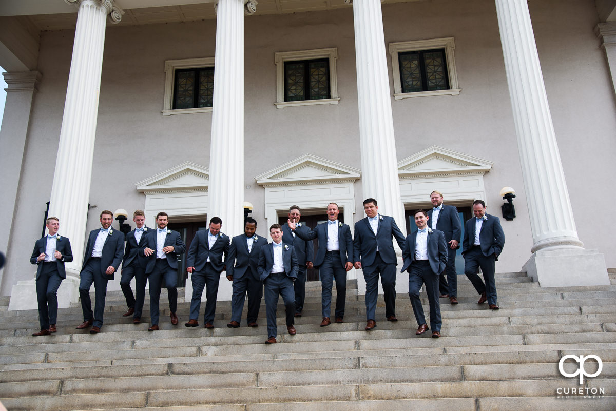 Groom and groomsmen walking down the steps at Grace Church.