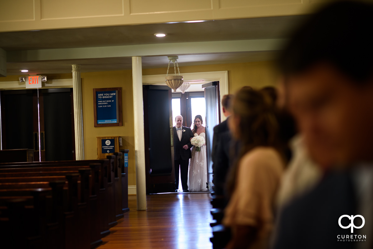 Bride making an entrance to the wedding at Grace Church in Greenville,SC.