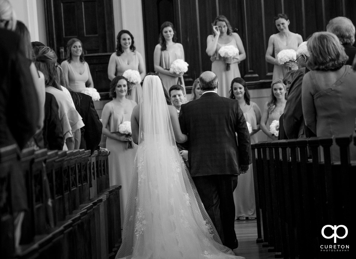 Groom watching his bride walk down the aisle at the wedding at Grace Church in Greenville,SC.