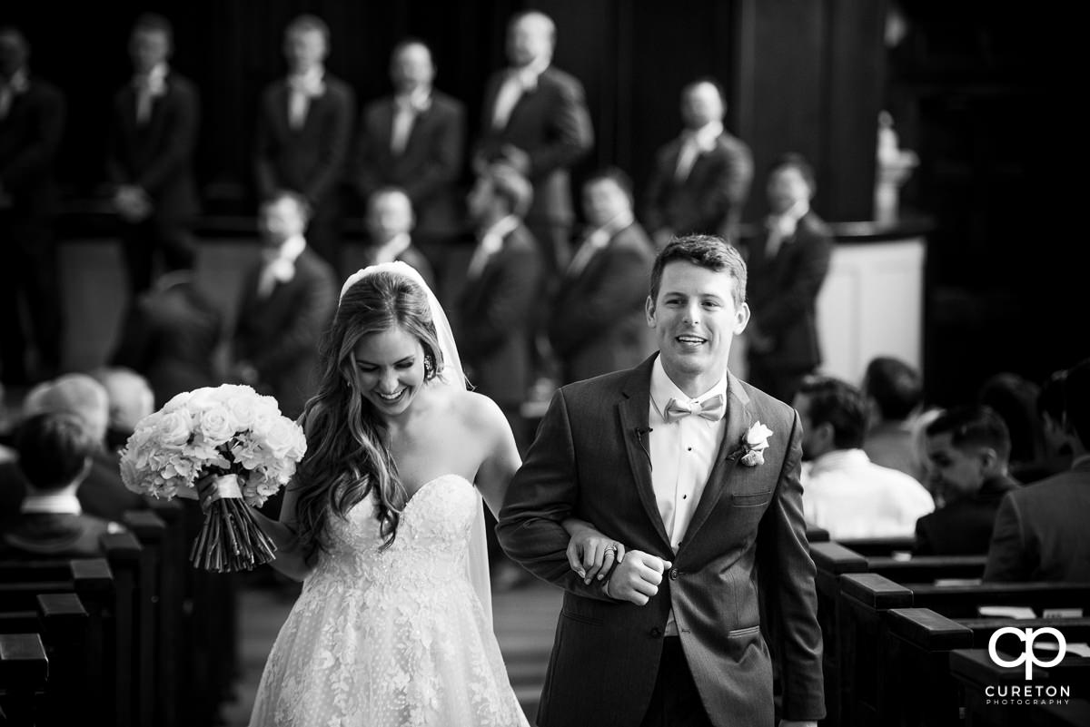 Bride and groom walking back up the aisle at their wedding at Grace Church in Greenville,SC.