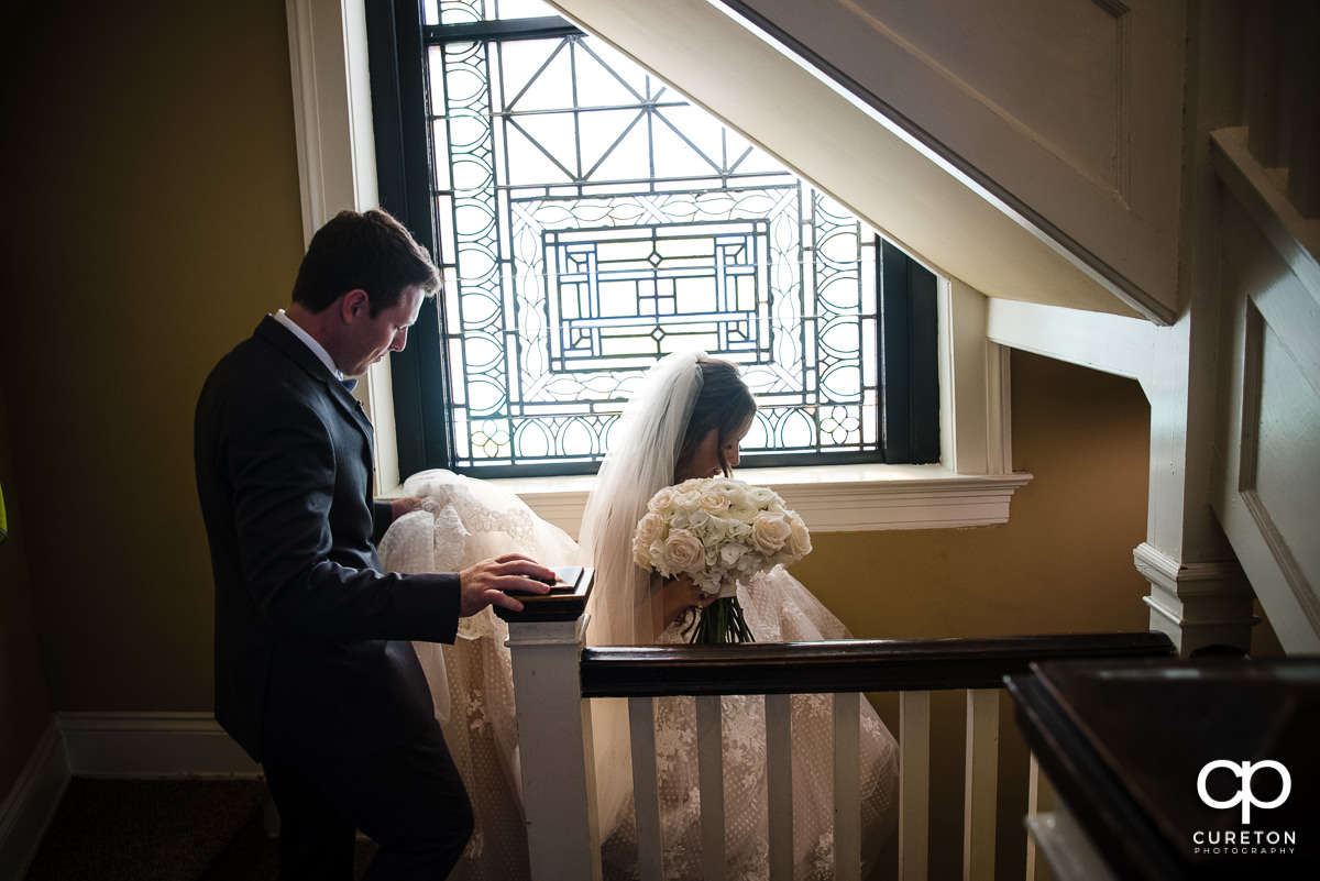 Groom helping the bride down some stairs at their wedding at Grace Church in Greenville,SC.