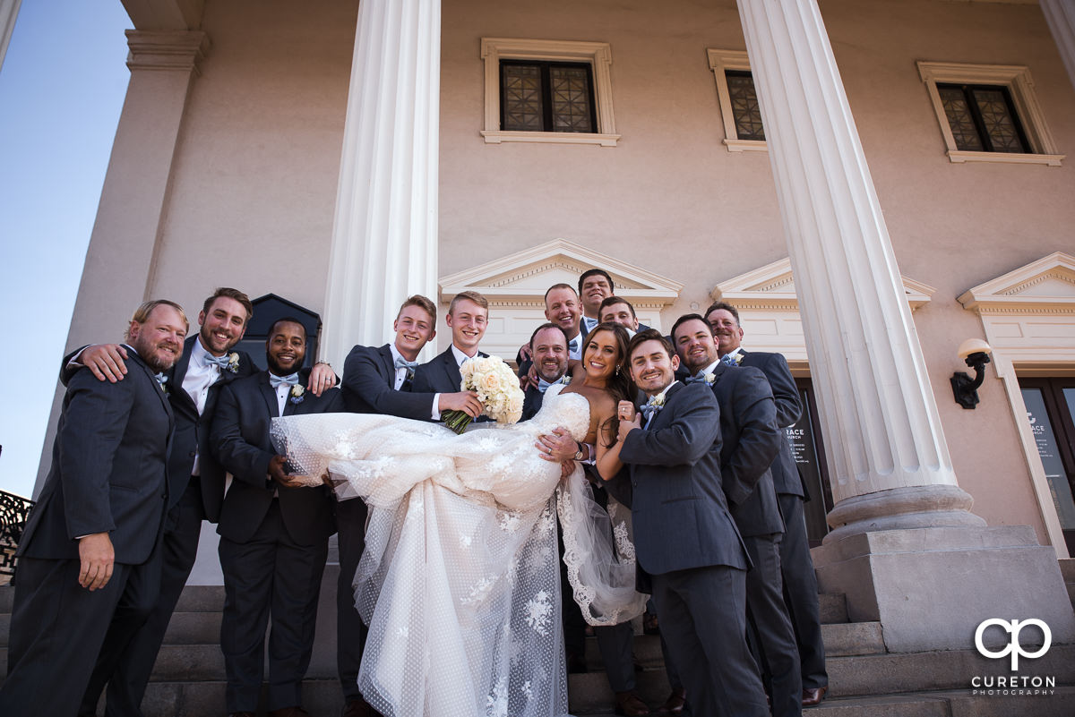 Groomsmen holding the bride up on the steps of Grace Church.