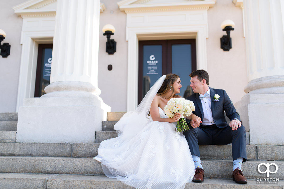 Bride and groom sitting on the steps after the wedding at Grace Church in Greenville,SC.