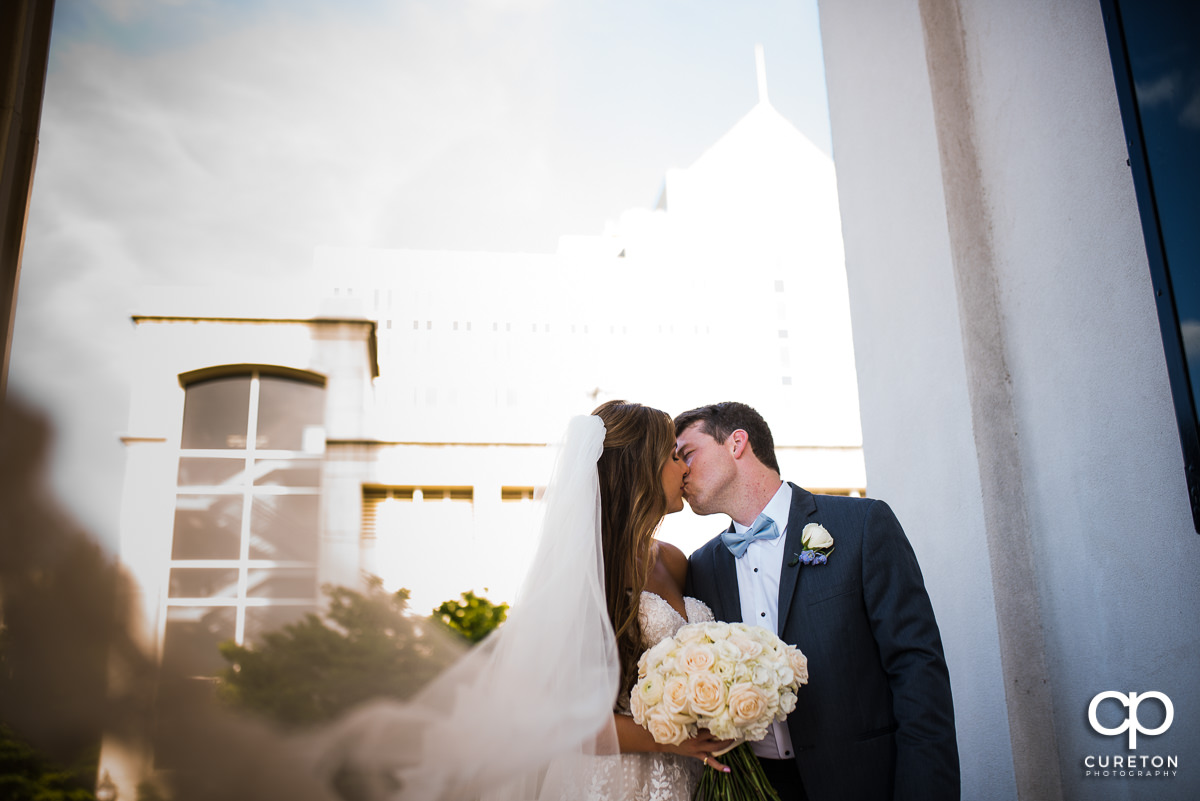 Bride and groom kissing as her veil blows into the wind in downtown Greenville,SC.