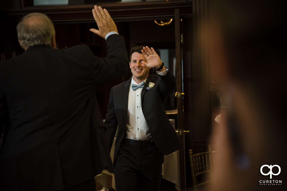 Groom giving a high five to a guest.