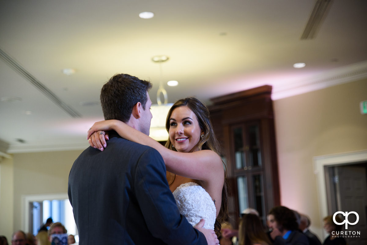 Bride smiling at the groom during their first dance at the Commerce Club wedding reception in Greenville,SC.