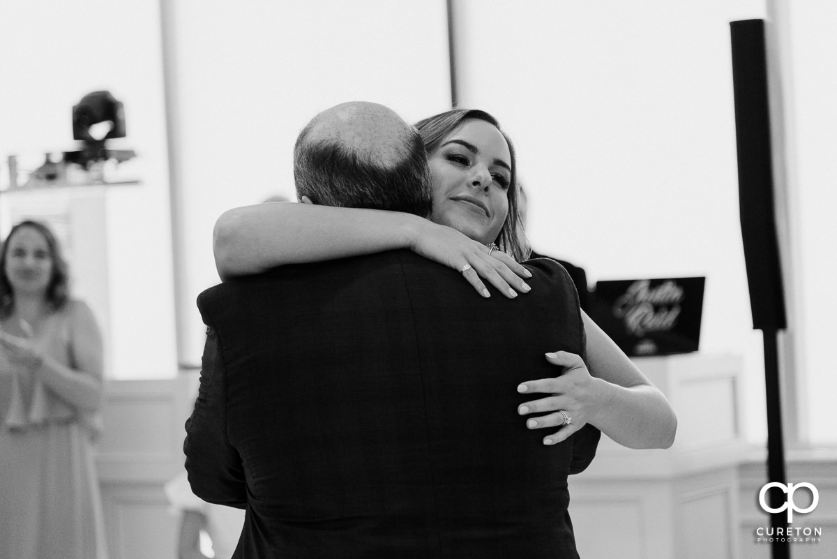 Bride hugging her dad after their dance at the Commerce Club wedding reception in Greenville,SC.