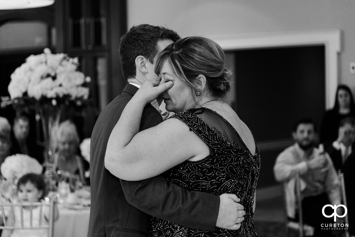 Groom's mom wiping tears away as she sahres a dance with her son at the Commerce Club wedding reception in Greenville,SC.