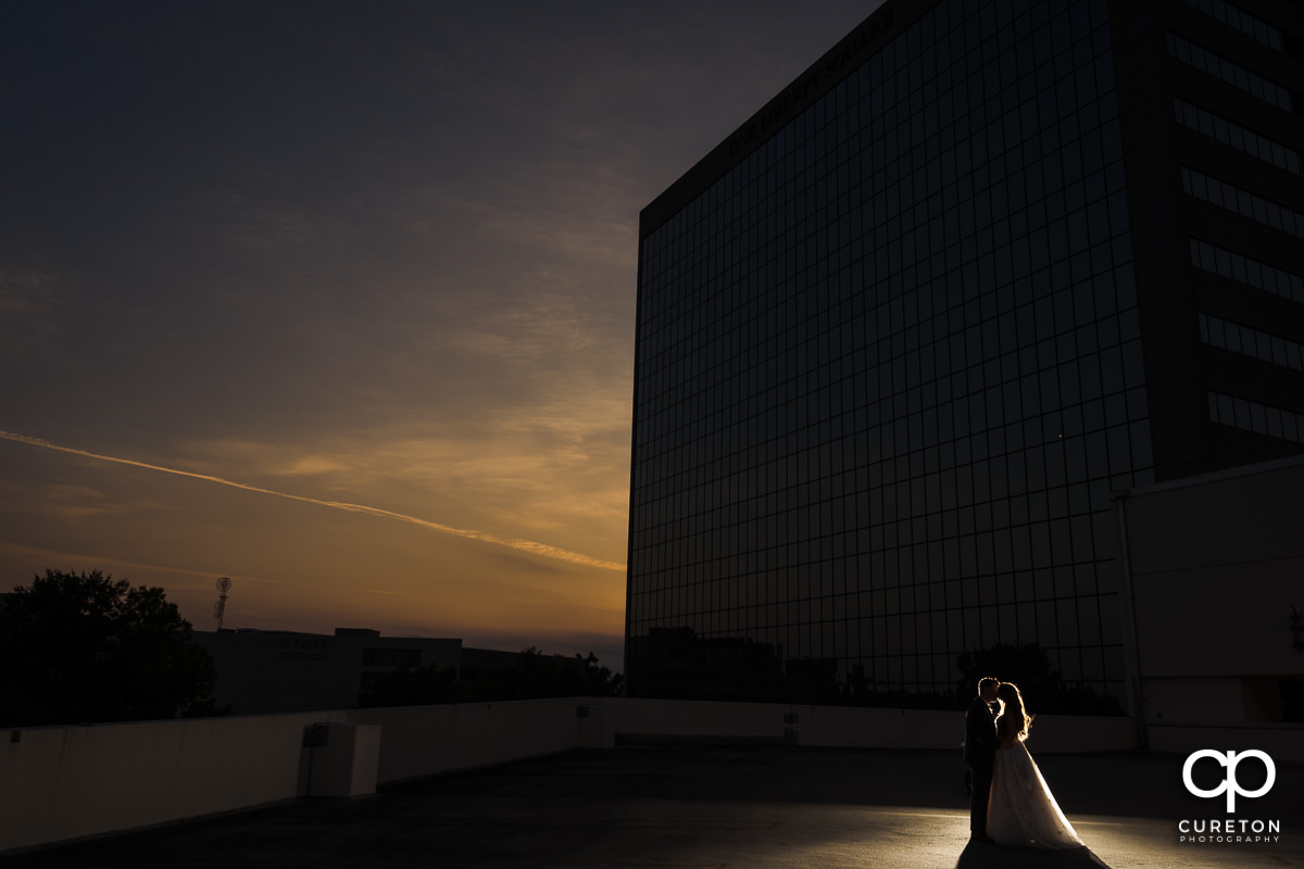 Bride and groom kissing at sunset on a rooftop at the Commerce Club wedding reception in Greenville,SC.