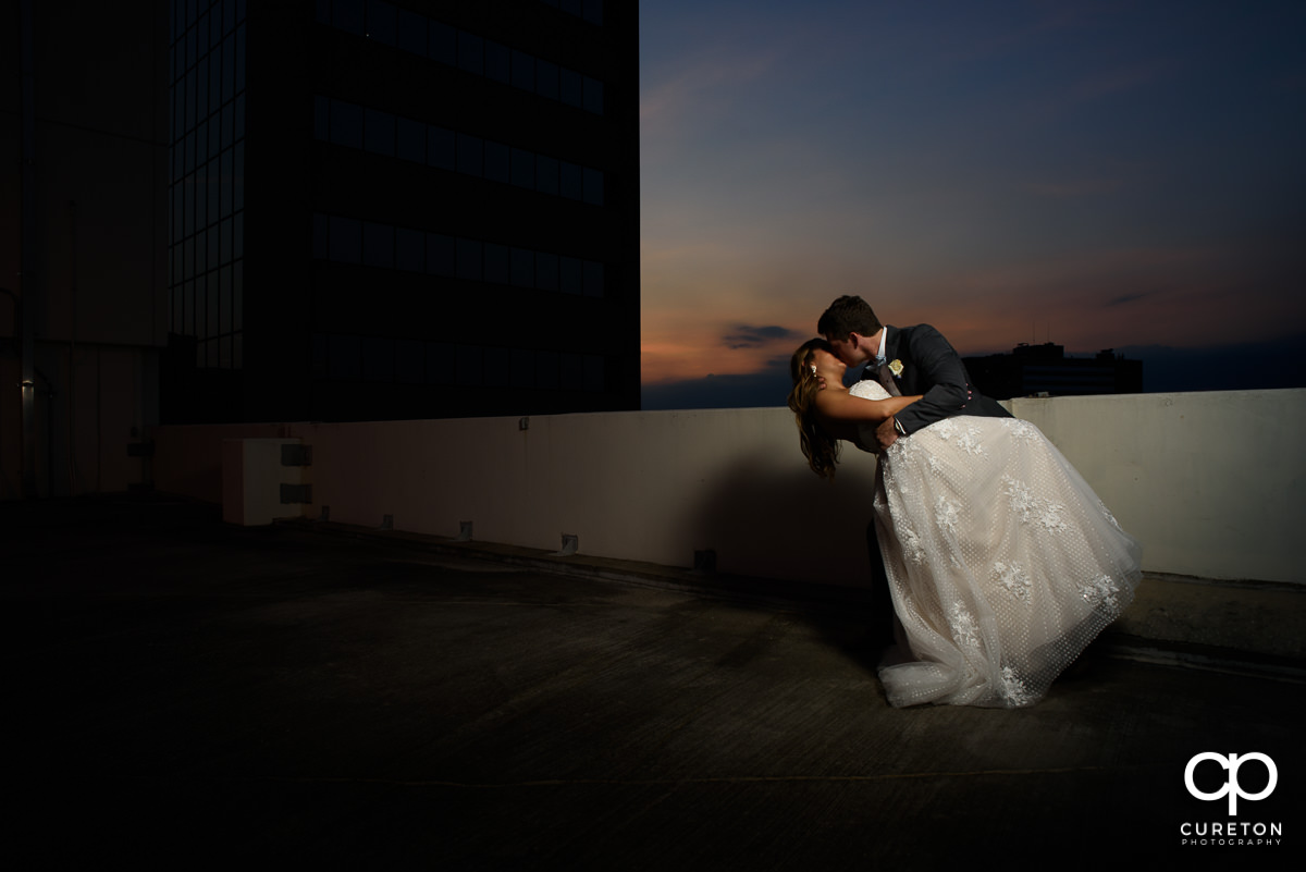 Groom dipping his bride at sunset at the Commerce Club wedding reception in Greenville,SC.