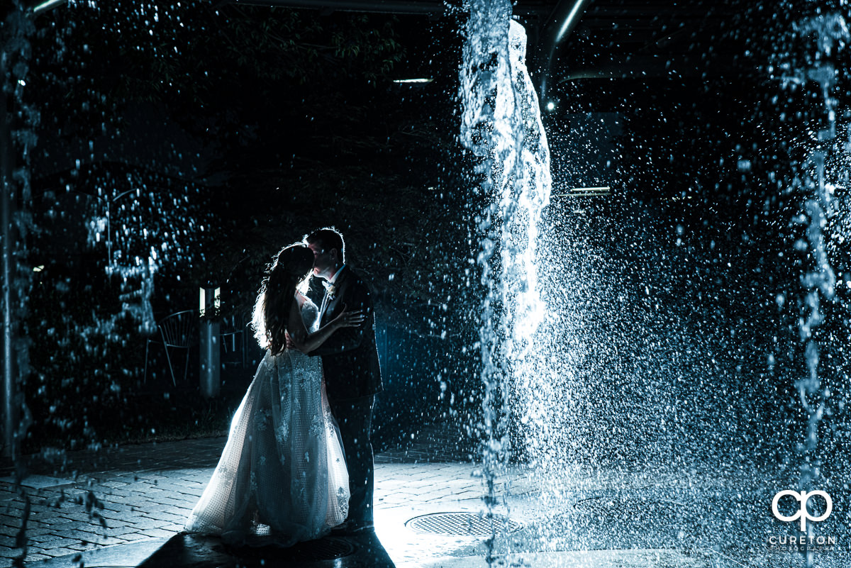 Bride and groom kissing in the fountains at the Commerce Club wedding reception in Greenville,SC.