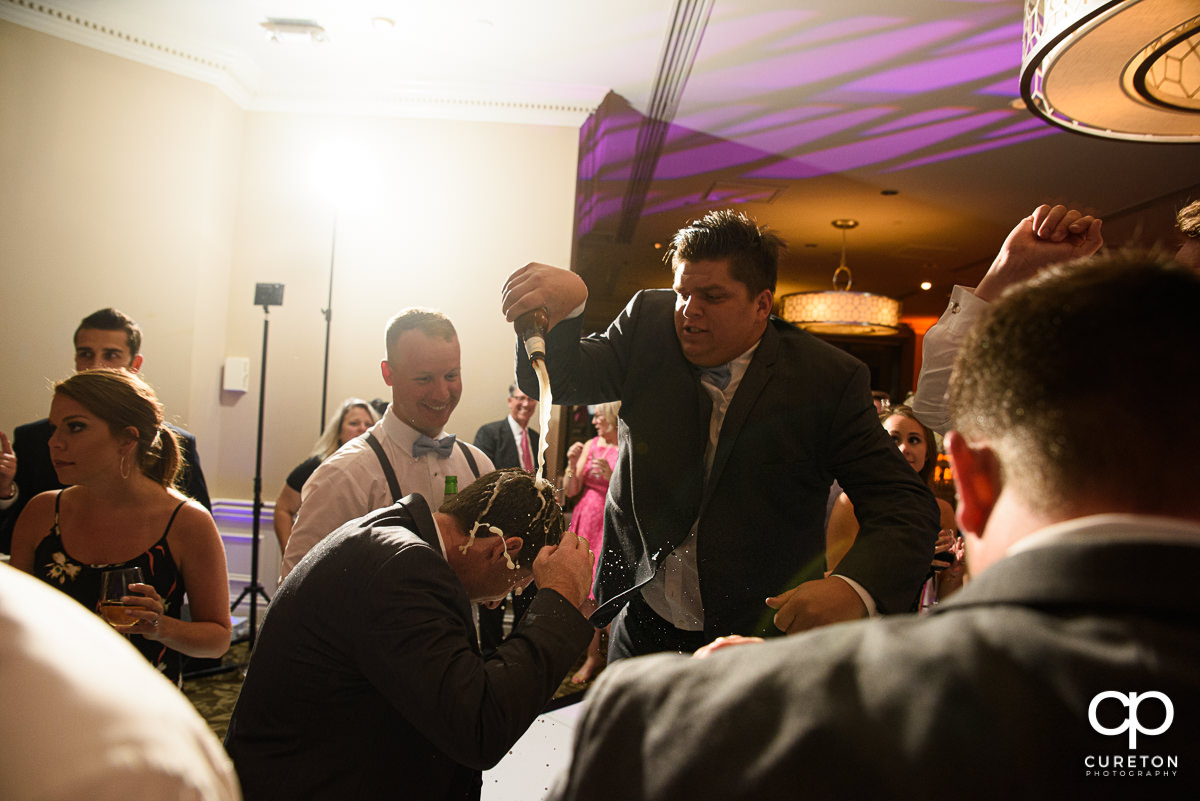 Groom getting a beer poured on his head.