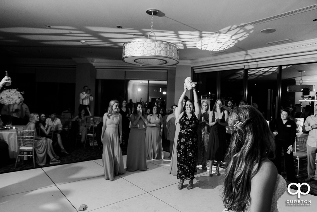 Bridesmaid catching her bouquet.