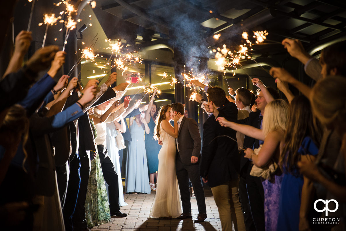 Bride and groom making an epic grand exit through sparklers at the Commerce Club wedding reception in Greenville,SC.