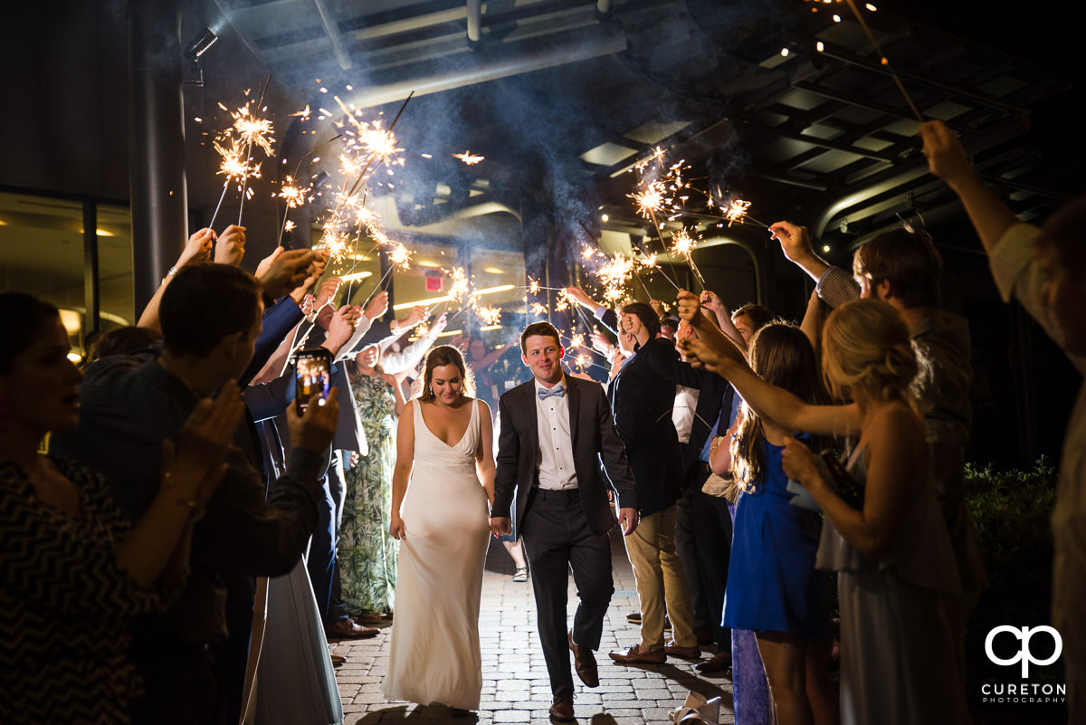 Bride and groom making a grand exit through sparklers at the Commerce Club wedding reception in Greenville,SC.