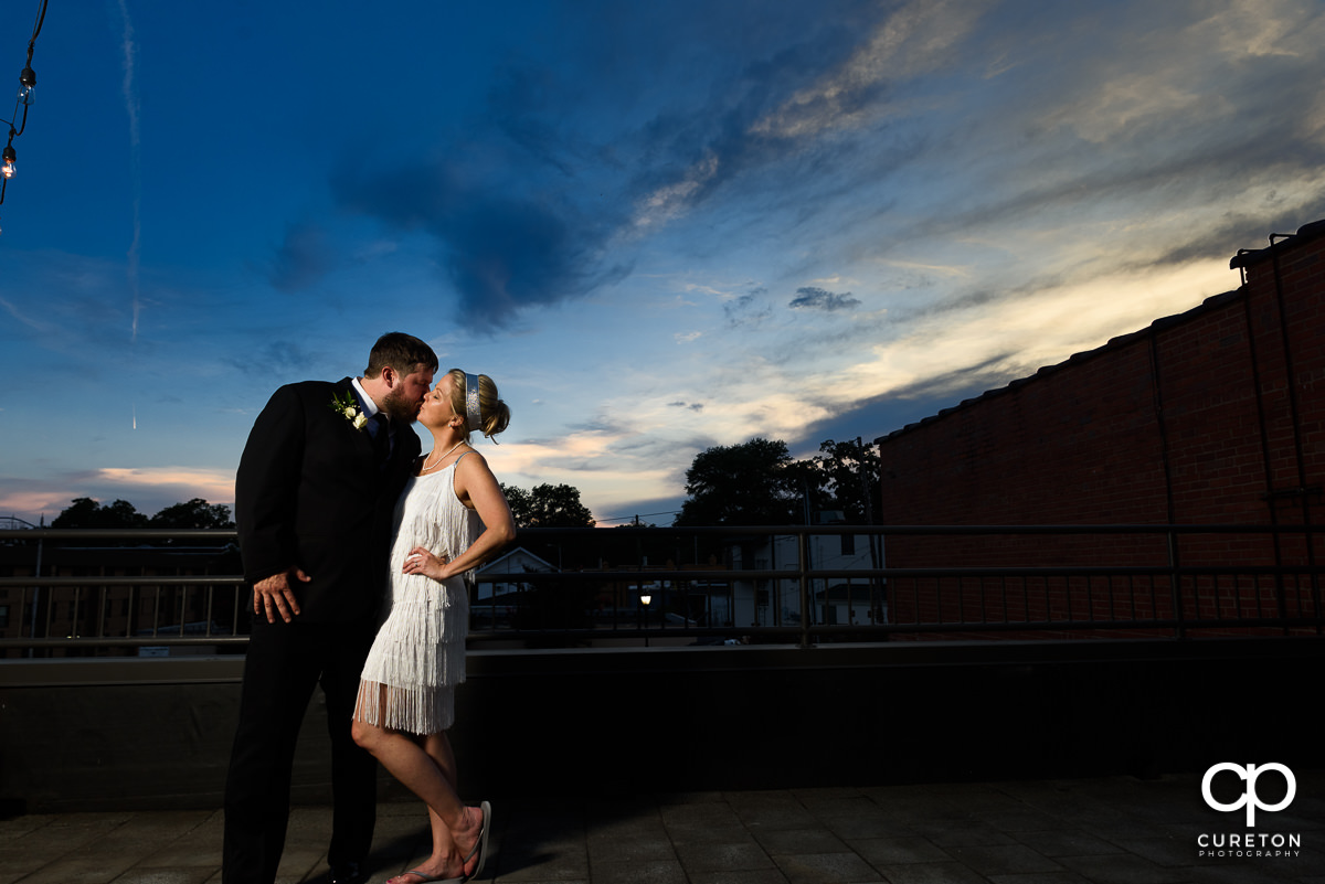 Bride and groom kissing on a rooftop in downtown Greer after outside of their Grace Hall wedding reception.